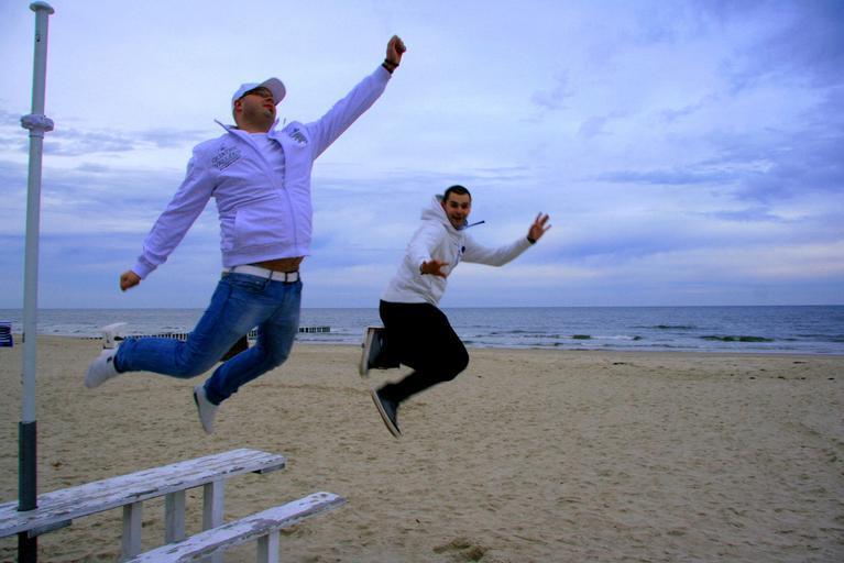 dva skákající muži na pláži