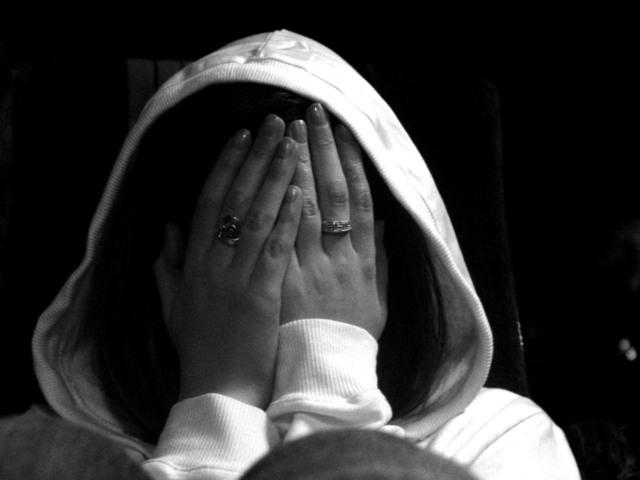 člověk zakrývající si tvář dlaněmi