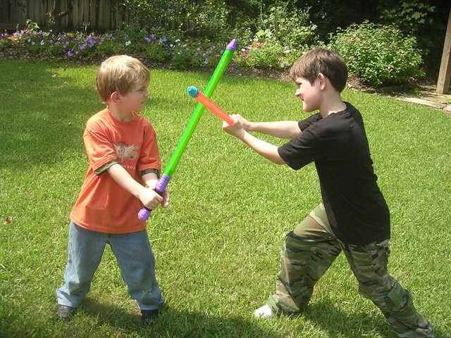 malí chlapci zápasí s meči na zahradě.jpg